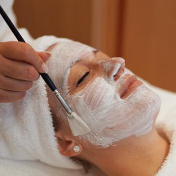 Einer Frau wird eine Gesichtsmaske aufgetragen